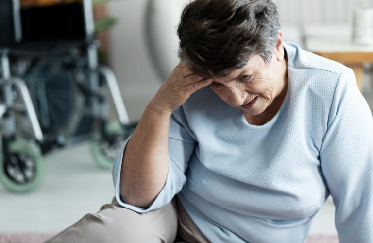 Senior woman in hospital or exam room holding head in pain