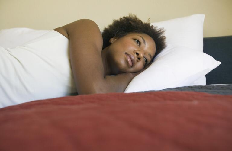 young-woman-laying-in-bed-awake