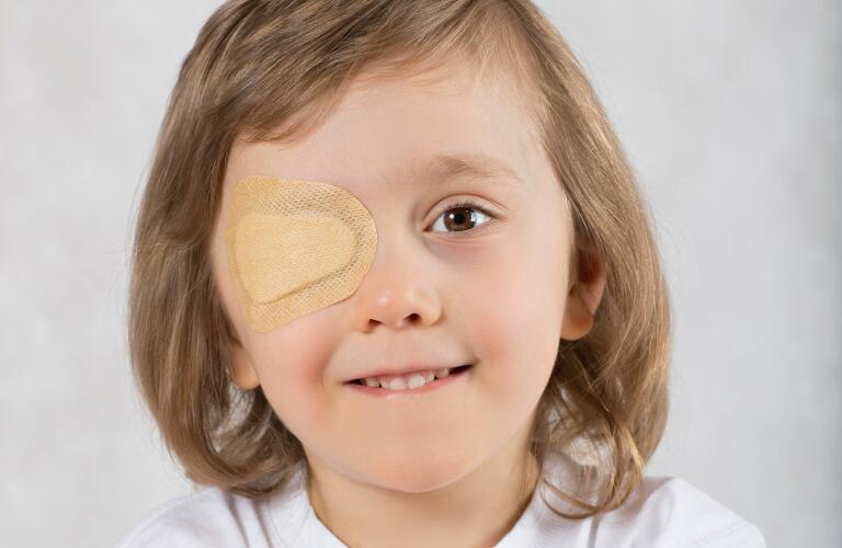 Boy with one eye covered with adhesive patch