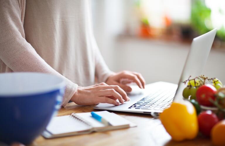 Woman looking something up online using a laptop computer in kitchen, with notebook and pen nearby