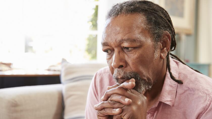 serious senior african american man sitting on couch