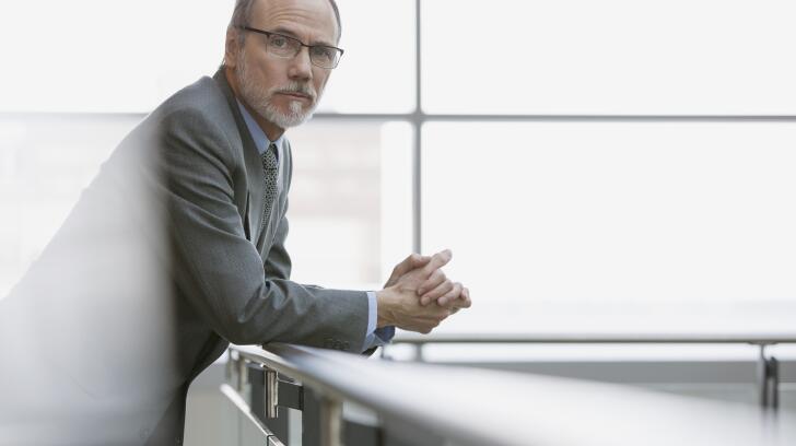 businessman-leaning-on-handrail