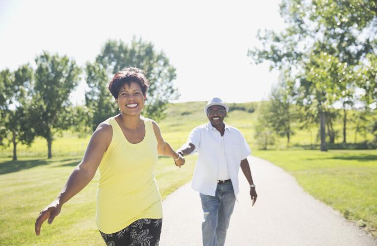 happy-couple-walking-on-path-outside