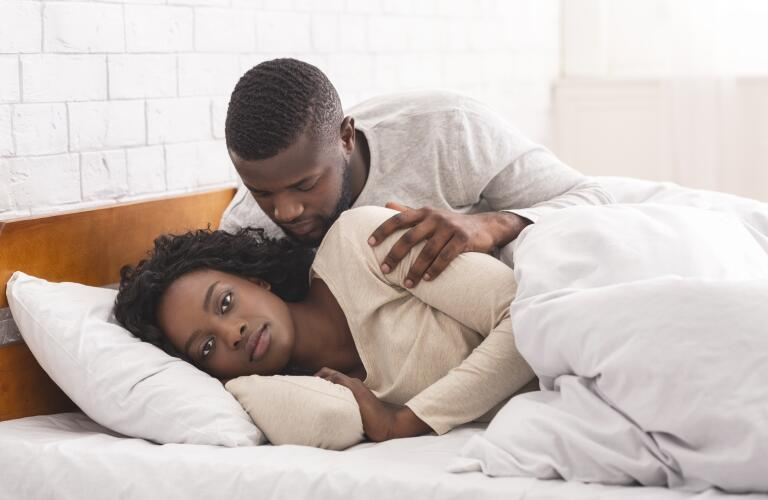 Woman ignoring husband in bed