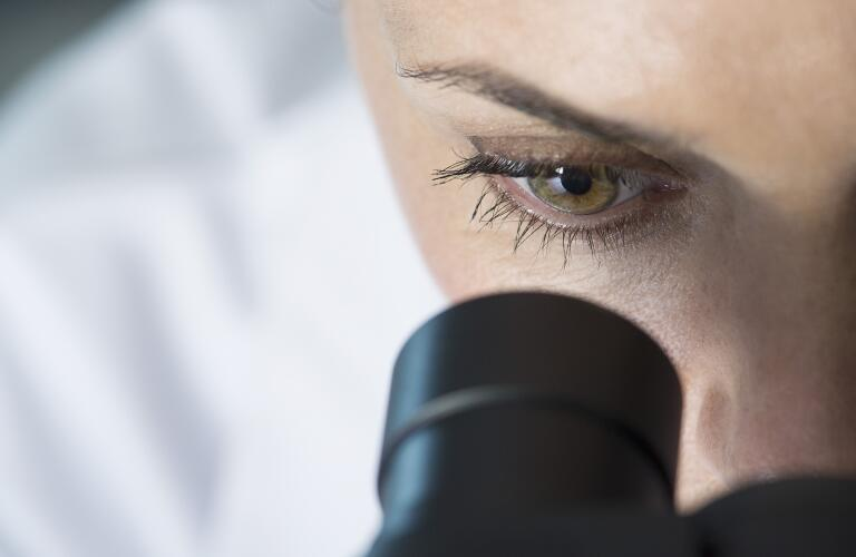 unidentified woman peering into microscope