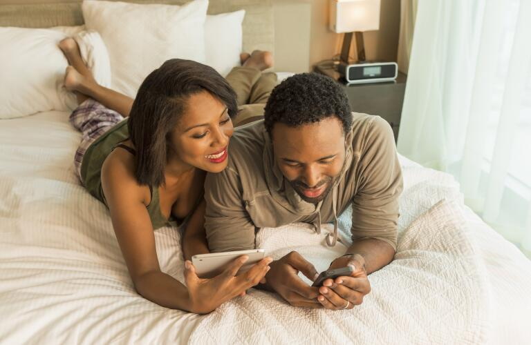 couple-talking-in-bed-looking-at-devices