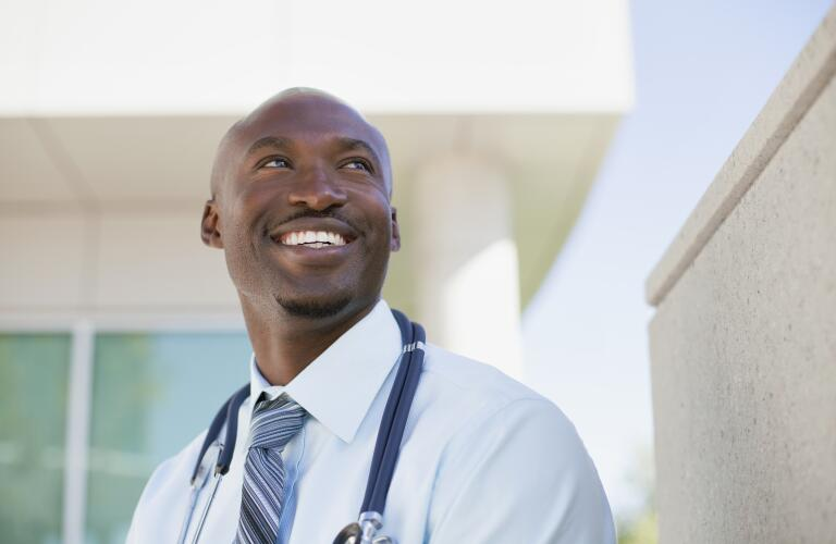 African american doctor standing outside looking up