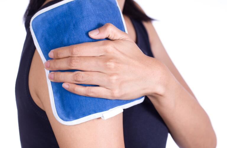 woman putting an ice pack on her upper arm