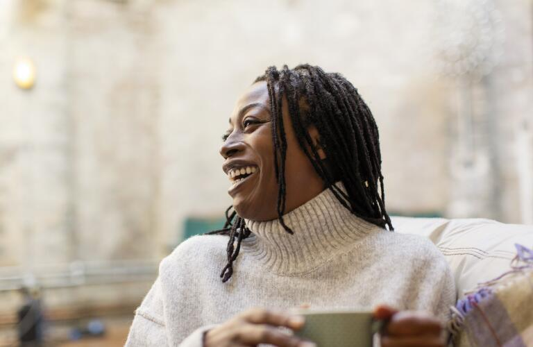 Middle aged African American woman smiling and laughing with cup of coffee