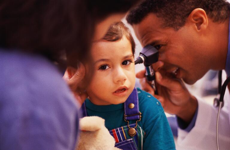 Doctor checking boy's ear; mother in foreground