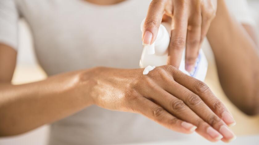 woman-putting-moisturizer-on-hand