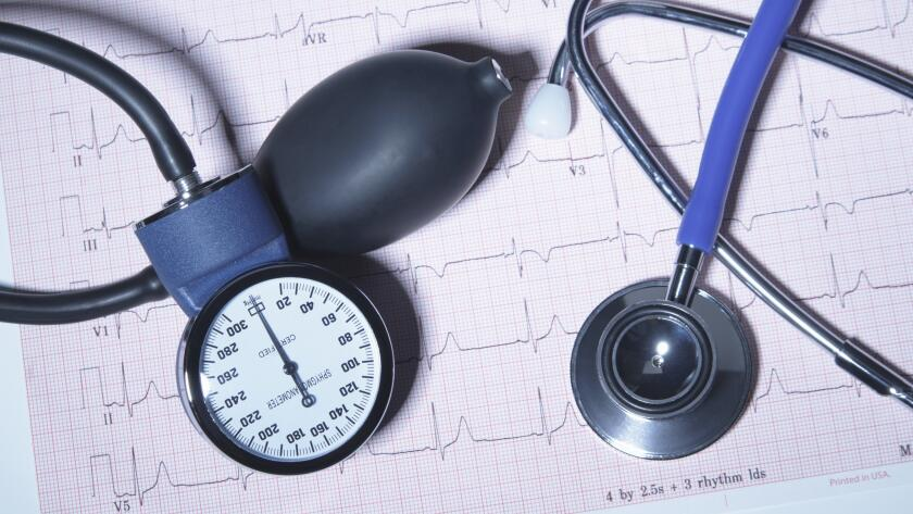 Acoustic stethoscope and blood pressure gauge on an electrocardiogram printout