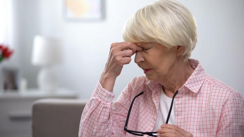 seniro Caucasian woman taking off eyeglasses and massaging bridge of nose