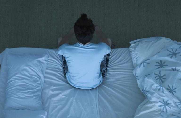 man-sitting-up-in-bed-having-trouble-sleeping