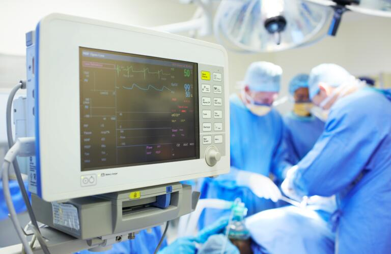 Close-up of heart monitor with surgeons in background in operating room
