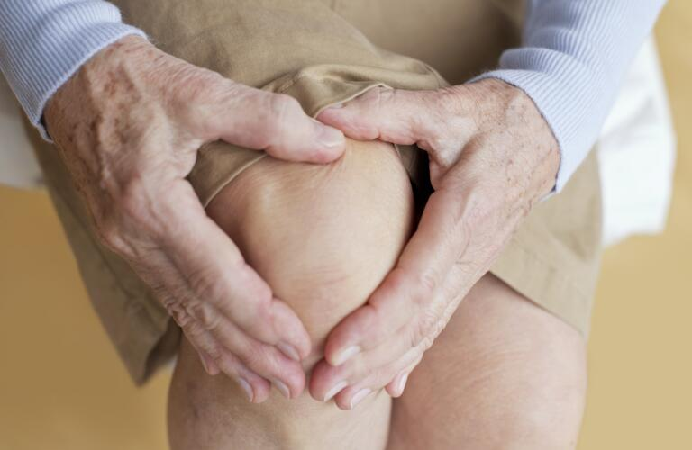 senior woman holding sore knee with arthritis