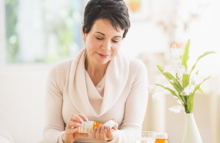 Middle aged Caucasian woman taking pill from prescription bottle