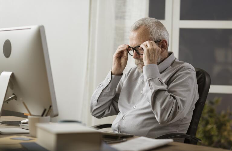 Senior man at computer adjusting eyeglasses