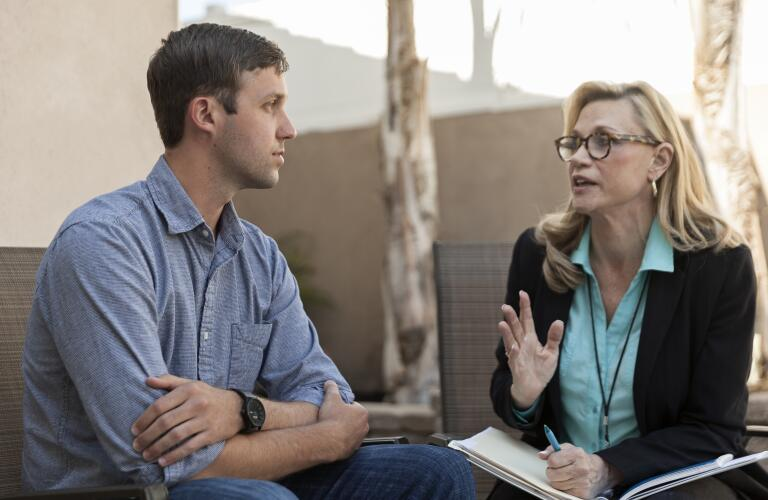 Young Caucasian man talking to middle aged female Caucasian therapist in outdoor setting