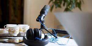 Podcast microphone and headphones set up near laptop on desk