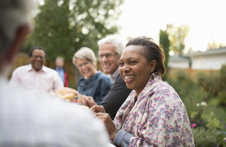 senior woman enjoying dinner outside with friends