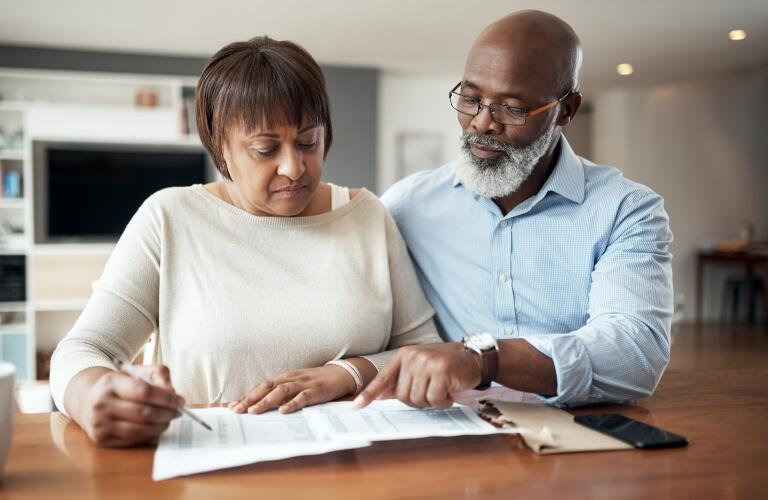 Senior African American couple reviewing paperwork at home