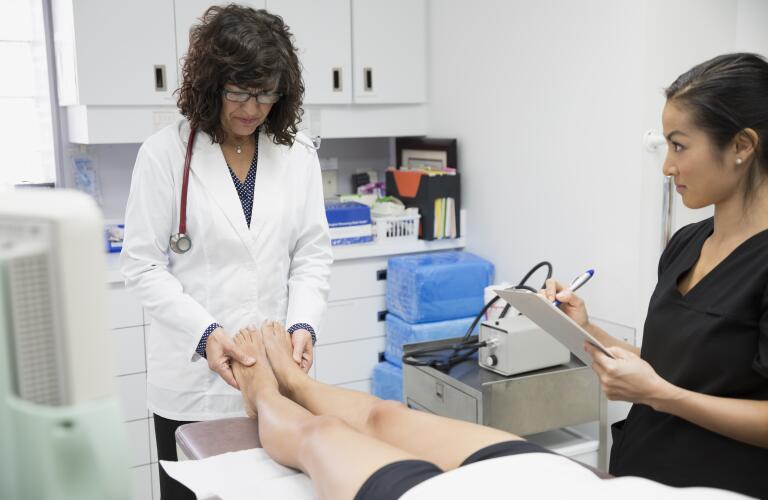 doctor examining patient's foot with nurse