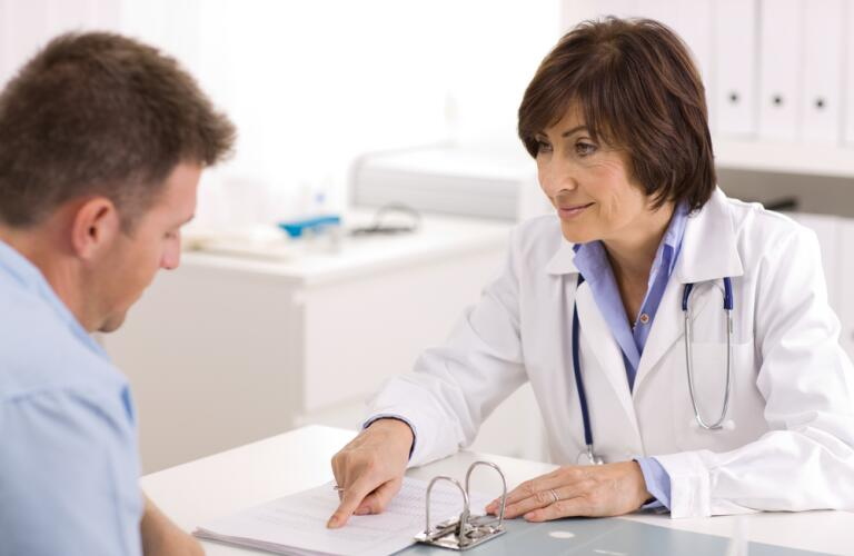 Female doctor with male patient looking at results