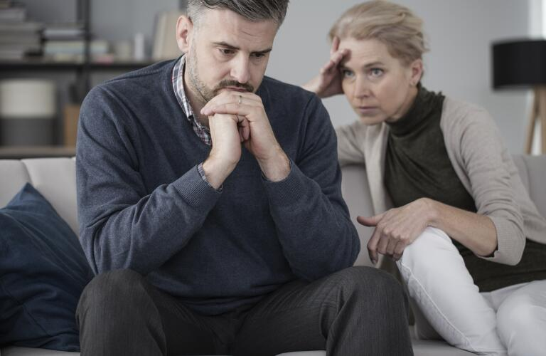 Middle aged Caucasian husband and wife on couch looking stressed and concerned