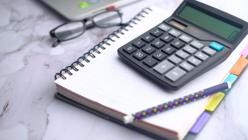 closeup calculator pen notebook eyeglasses and laptop on office table
