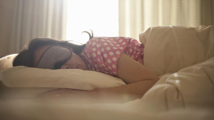 woman-wearing-sleep-mask-on-bed