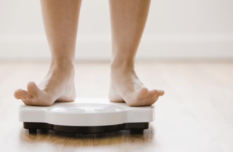 woman-standing-on-weight-scale