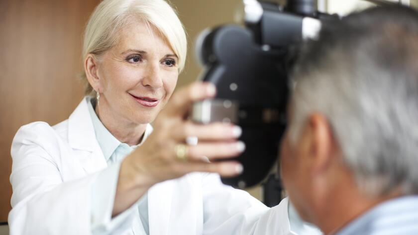 female eye doctor checking patient's vision