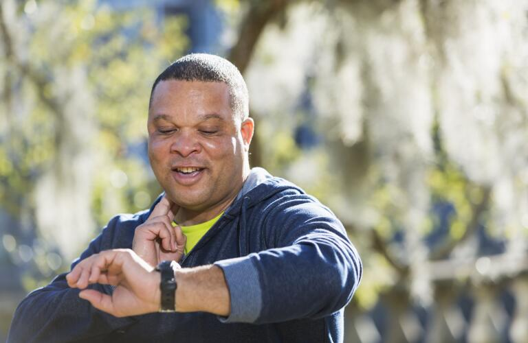 smiling middle age man checking pulse while exercising outside