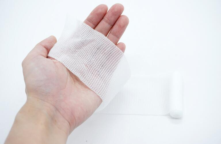 hand holding wound dressing for injury