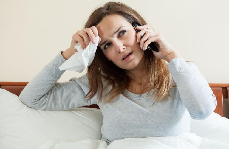 woman talking on phone while in bed with cold or flu