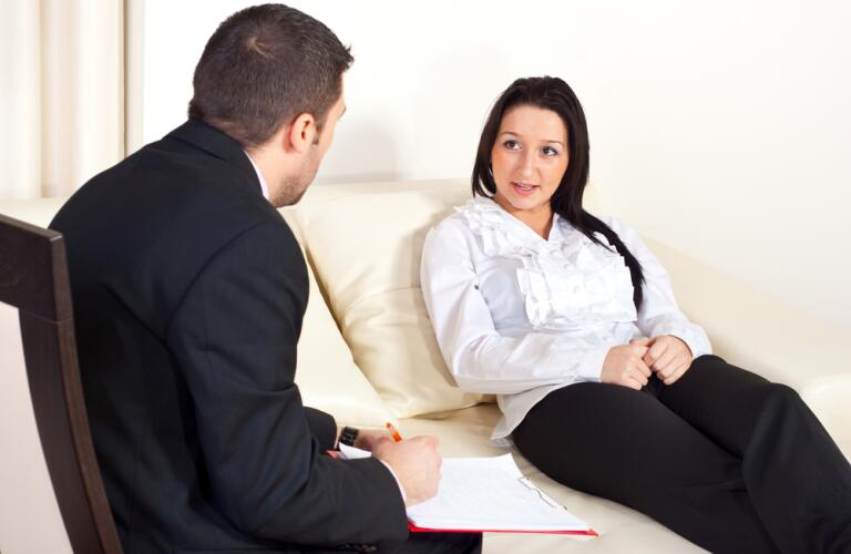 Woman sitting on couch talking with psychologist