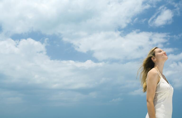 woman-standing-outside-breathing-fresh-air-with-sky-as-background