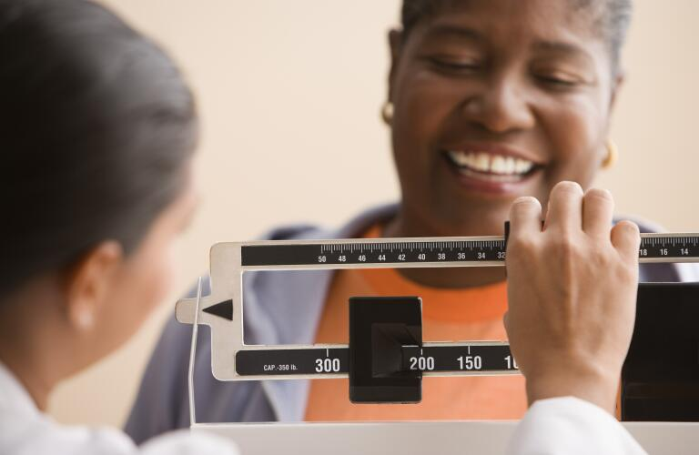 Older African American woman smiling on scale as doctor or nurse checks weight