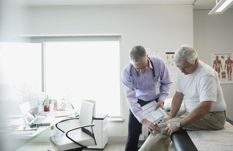 Older man with knee pain with doctor