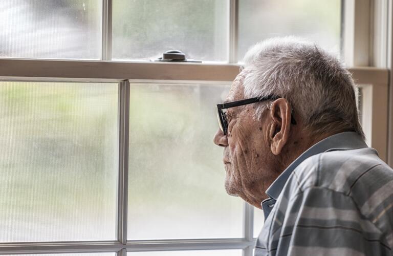 senior-man-staring-out-window