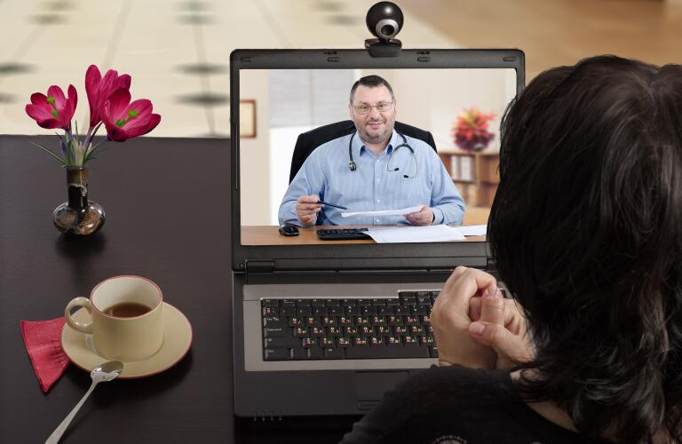 Female patient having telemedicine appointment with male doctor over laptop camera