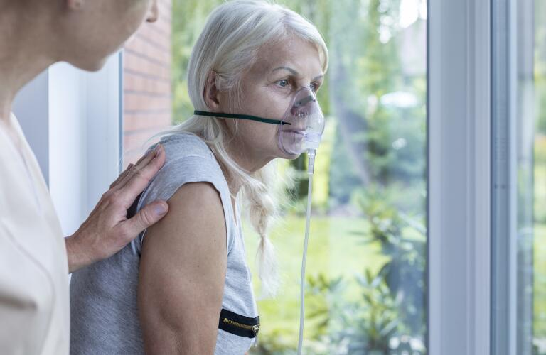 nurse supporting sick senior woman with oxygen mask and pale skin, bluish lips (cyanosis)