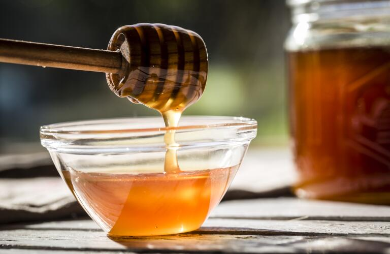 honey dripping off honey spoon into bowl
