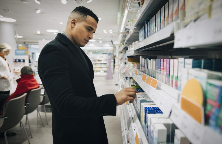 Young Hispanic man looking at shelf of pharmacy