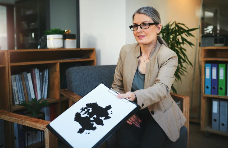 photo of a mature female psychologist conducting an inkblot test during a therapeutic session