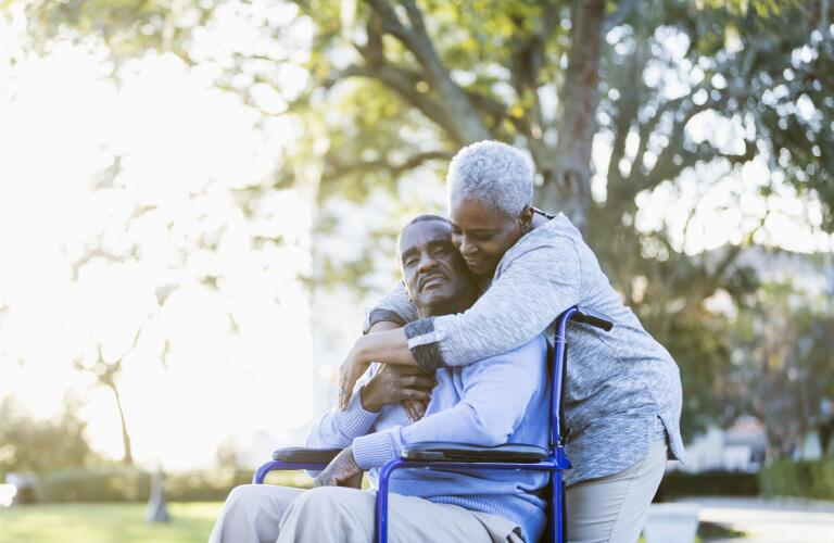 Senior African American man in wheelchair being hugged by wife outdoors in park