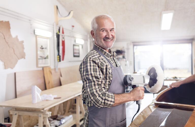 Senior male carpenter using a sander