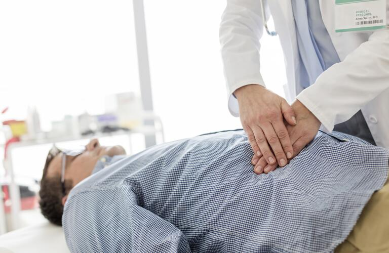 doctor examining patient's stomach