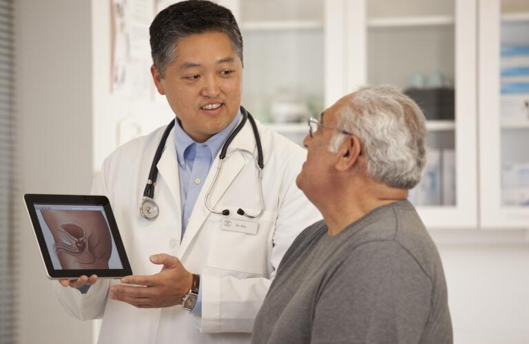 doctor using digital tablet to discuss prostate anatomy with patient